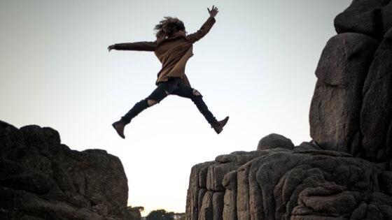 Ser valiente. Joven saltando entre rocas